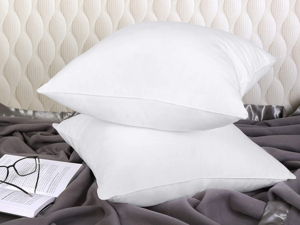 2 white pillows on bed with reading glasses and book