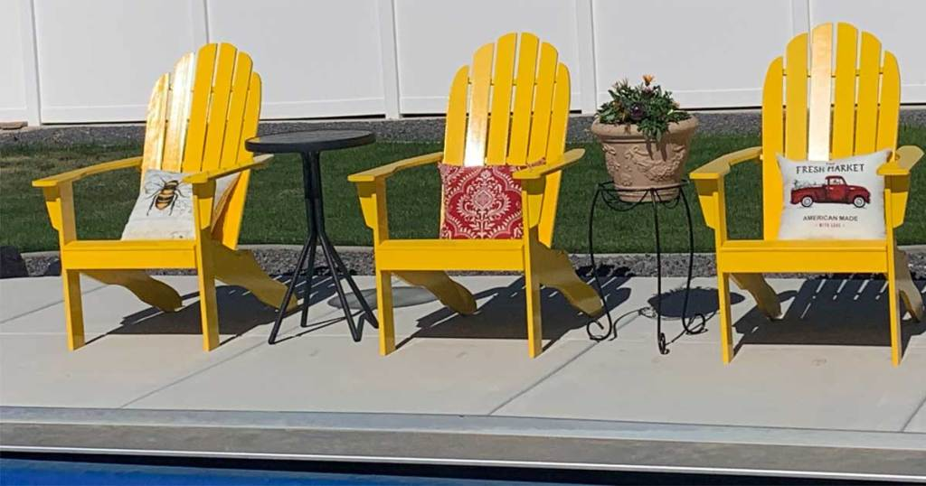 three chairs poolside with red pillow