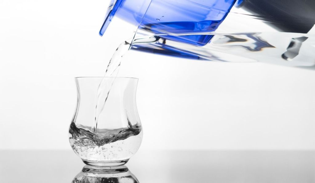 A water filter pouring into a clear glass