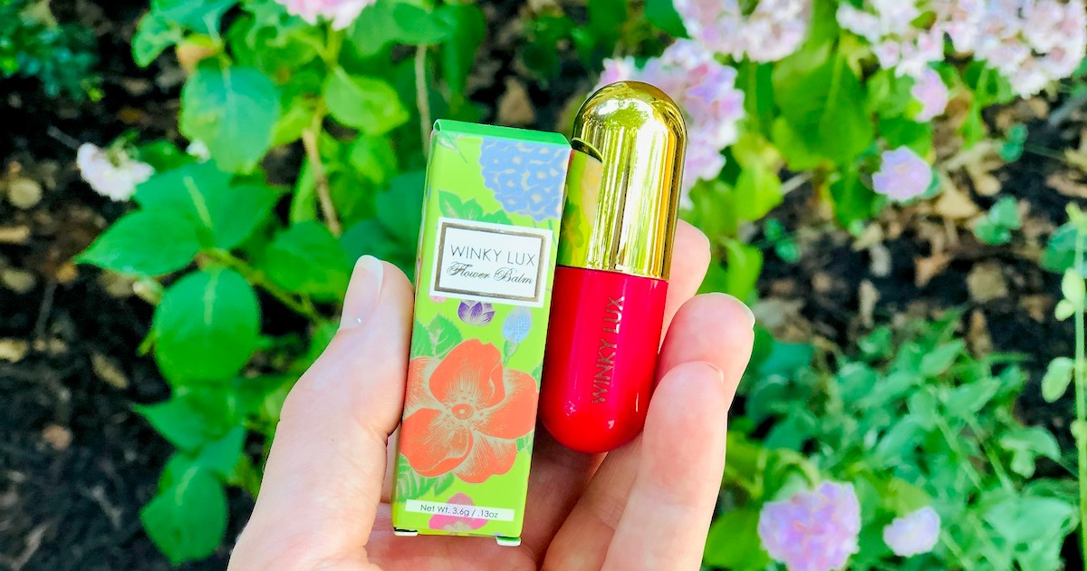 hand holding a hot pink and gold lip balm in front of flower garden