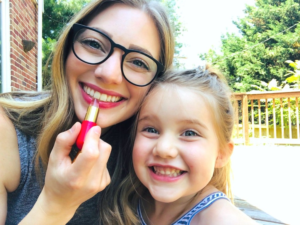 woman applying lipstick with smiling girl next to her