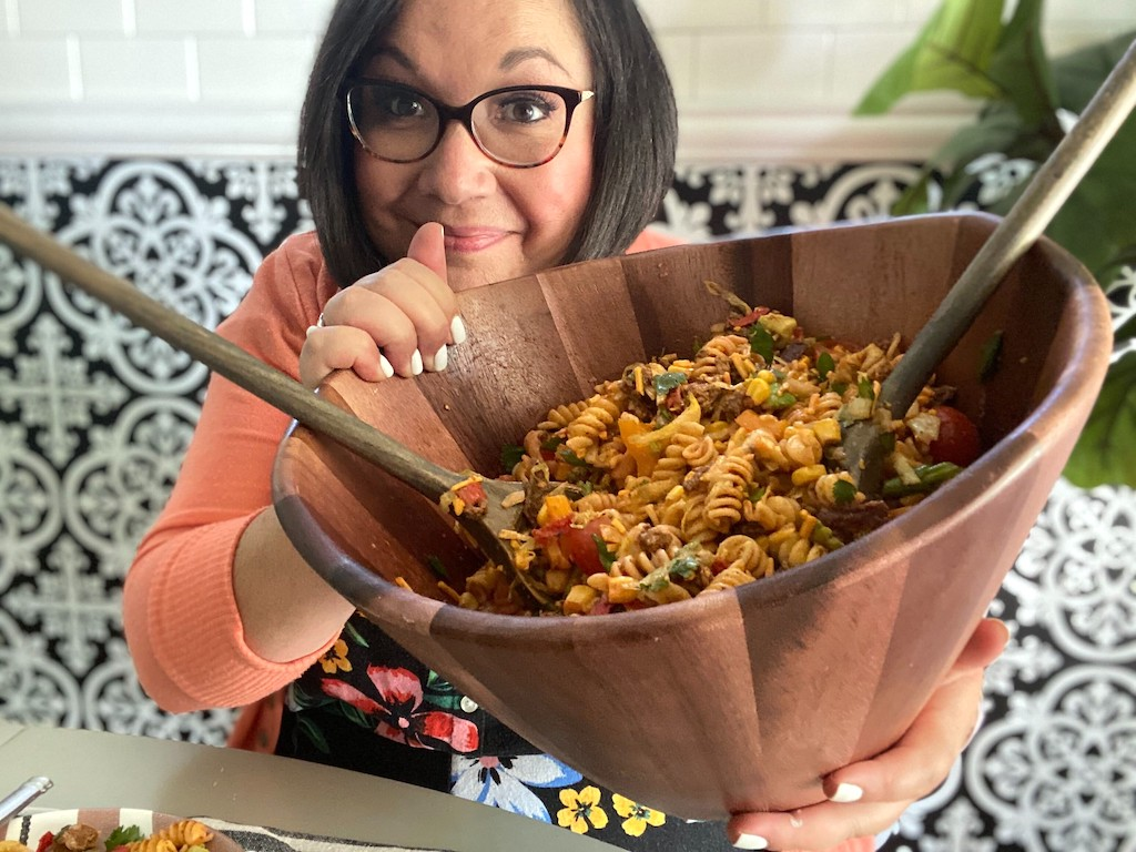 woman holding large wood bowl filled with taco pasta salad