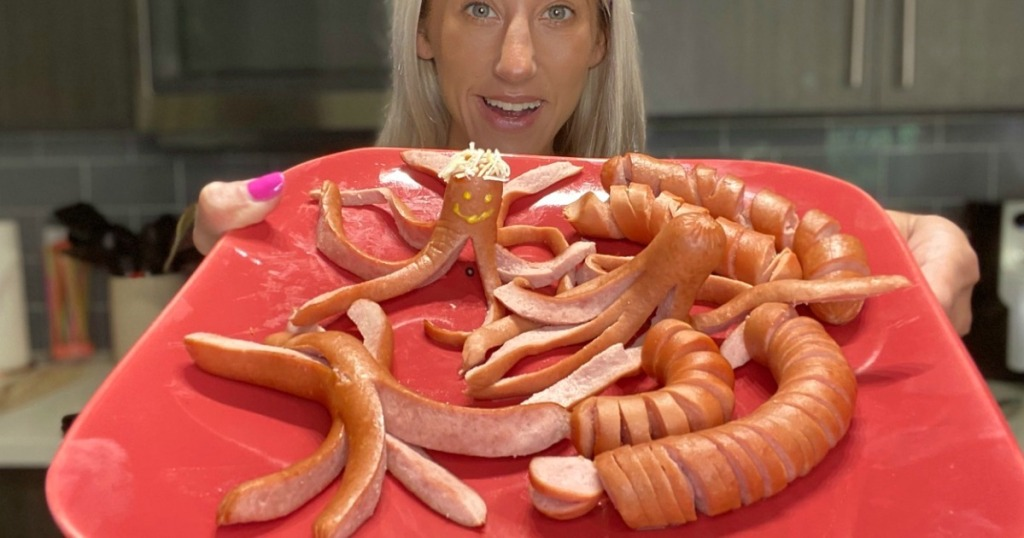 woman holding plate with silly and fun hot dogs
