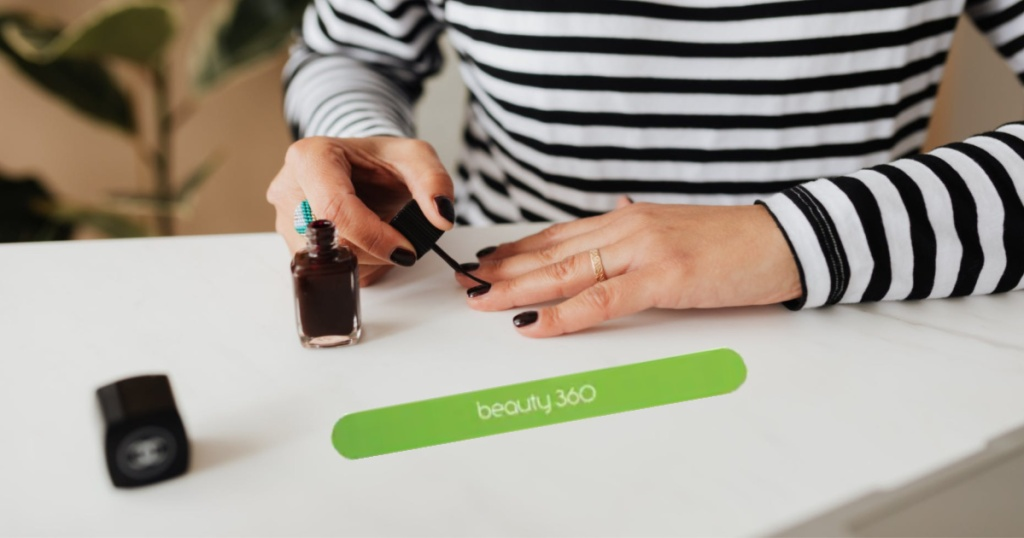 woman painting nails with emery board on table