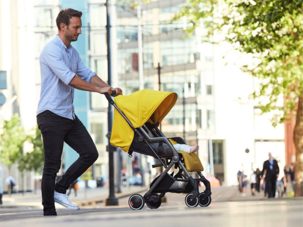 yellow diono traverze editions stroller pushed by man
