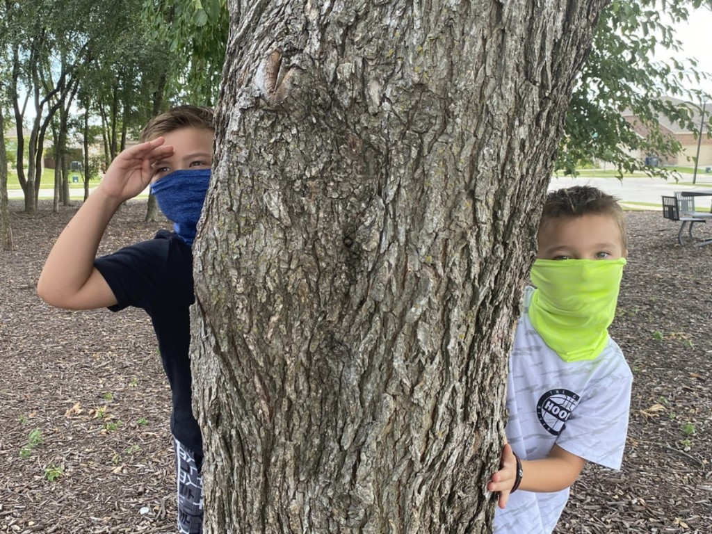 boys hiding behind tree wearing gaiter masks