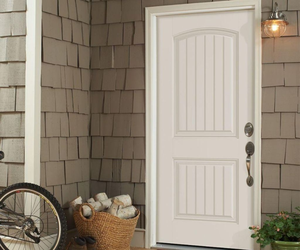A front porch with a box and bicycle next to the front door
