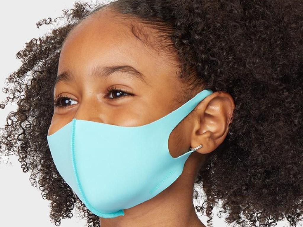 little girl wearing a light blue reusable face mask