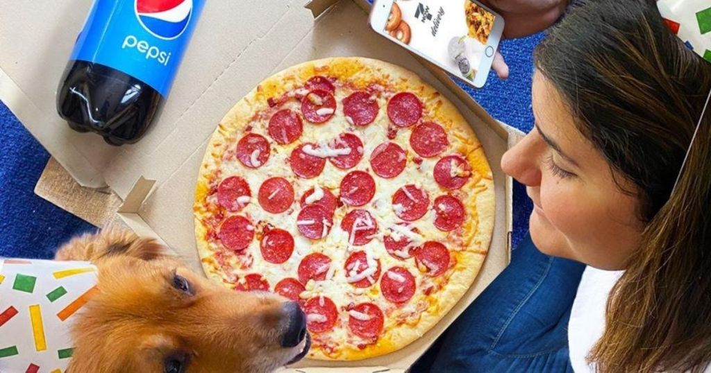 woman and her golden retriever with a pepperoni pizza