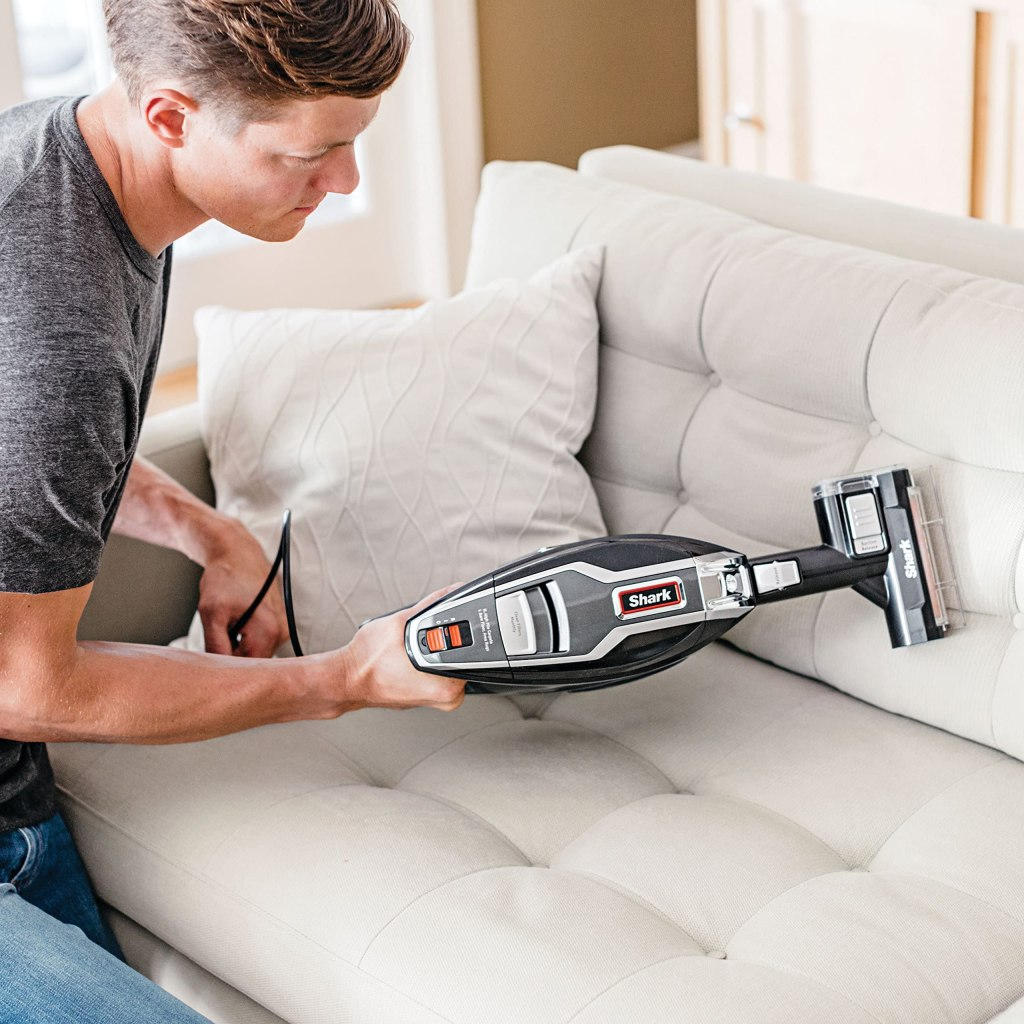 man holding a hand held shark vacuum cleaner on a white couch