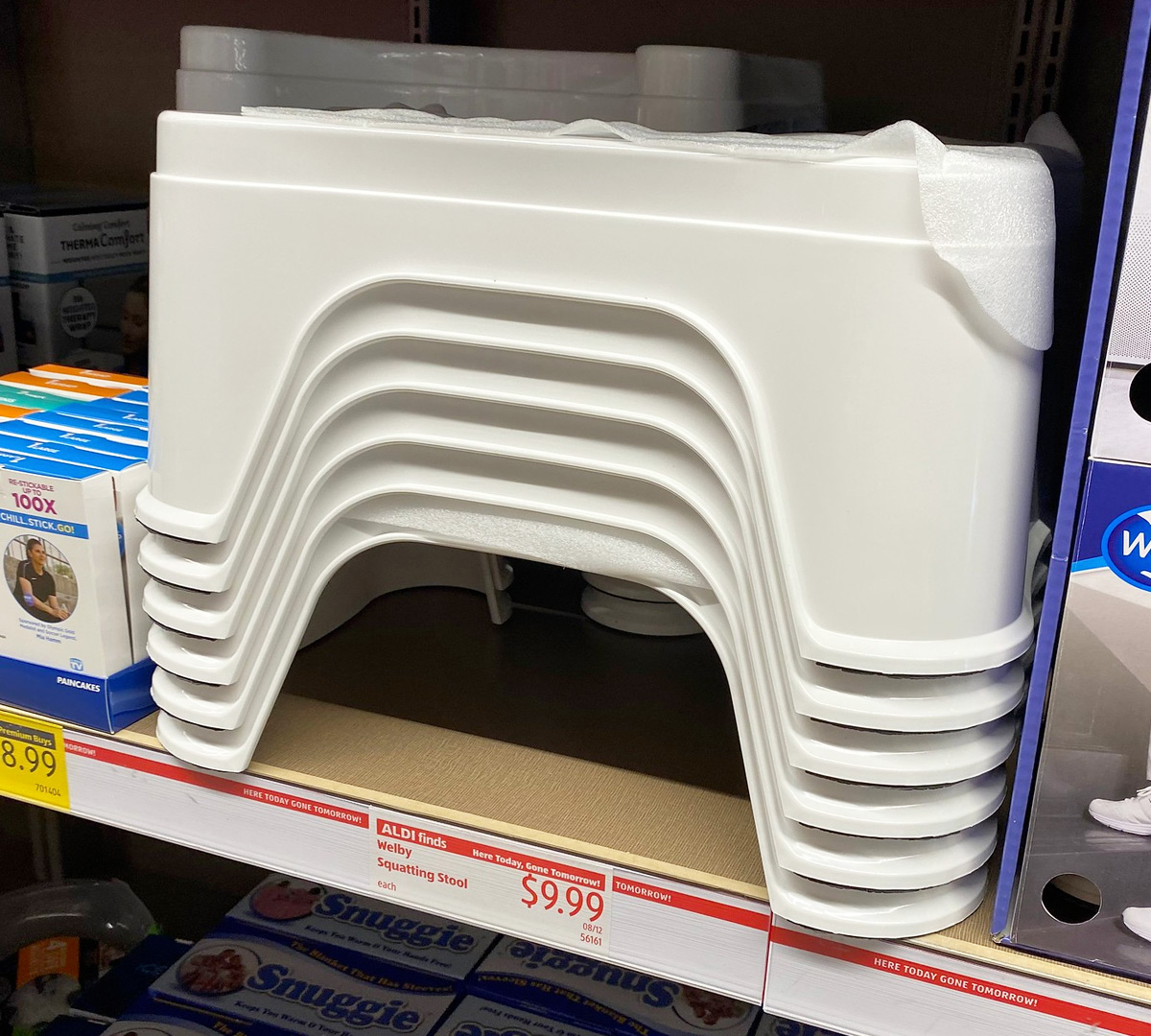stack of white bathroom squatting stools on an ALDI store shelf