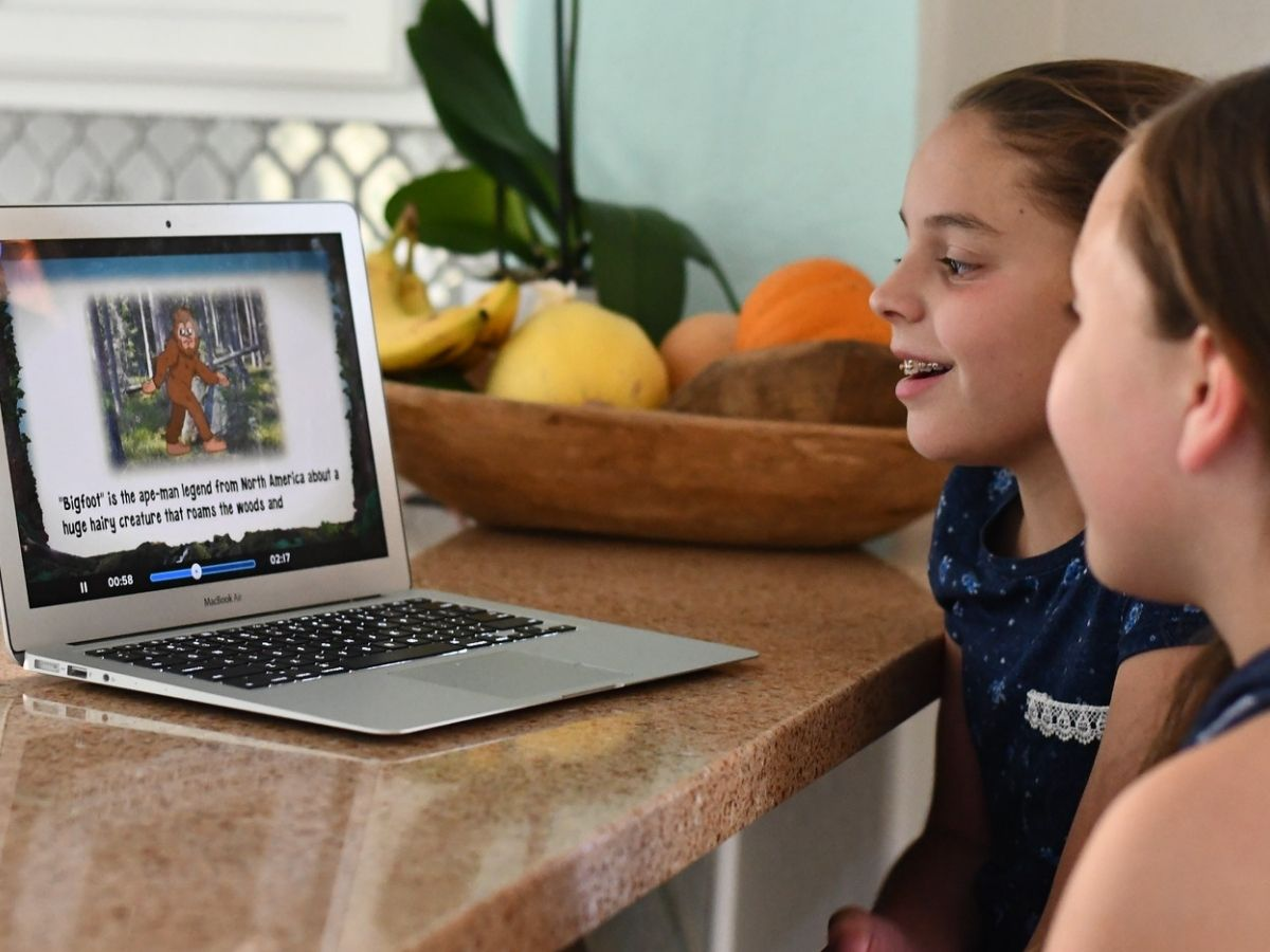 Two girls playing Adventure Academy on a laptop in a kitchen