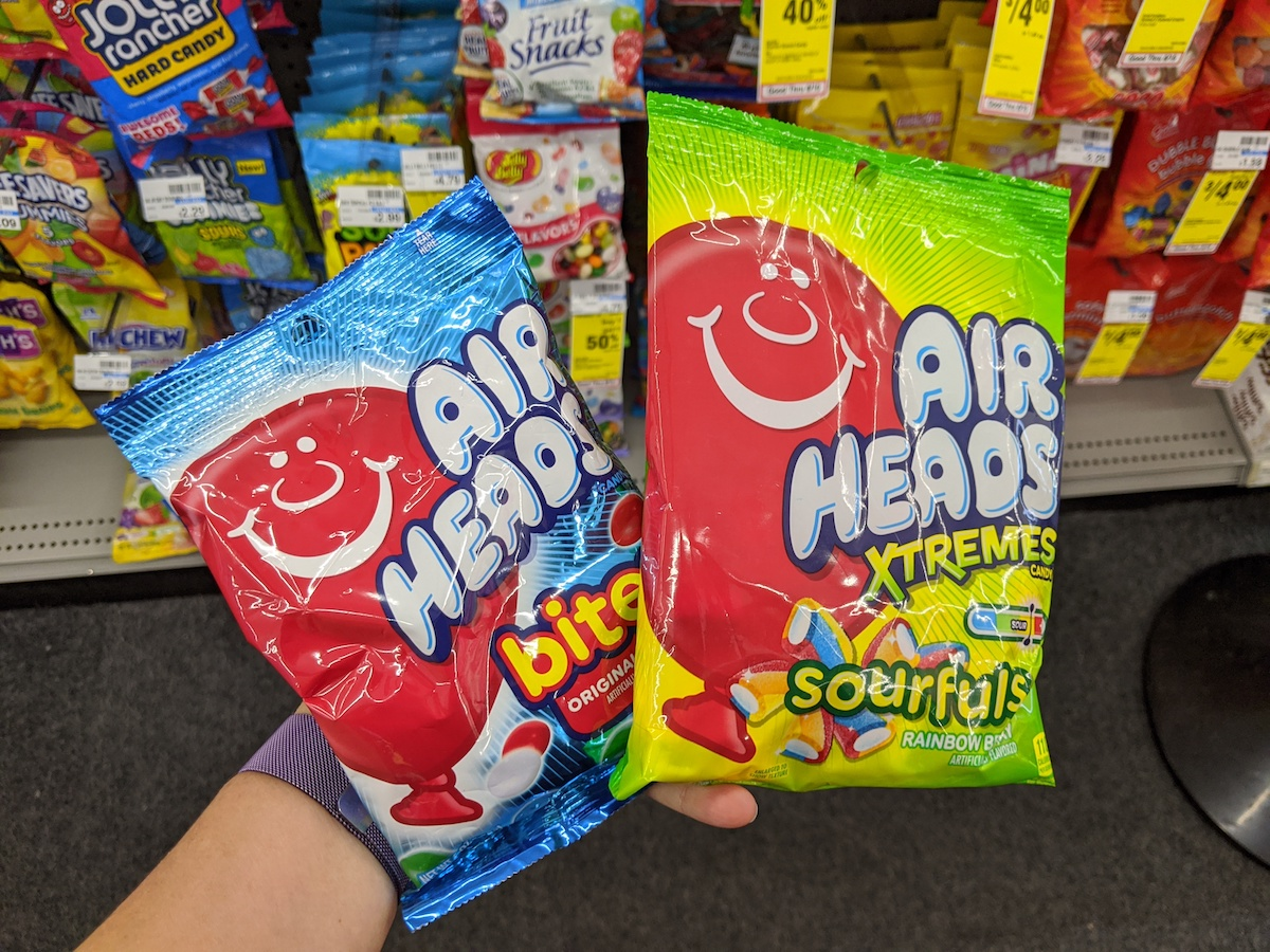 hand holding two packages of Airheads