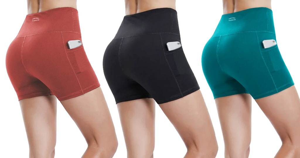 three women modeling workout shorts with pockets in red, black, and teal colors