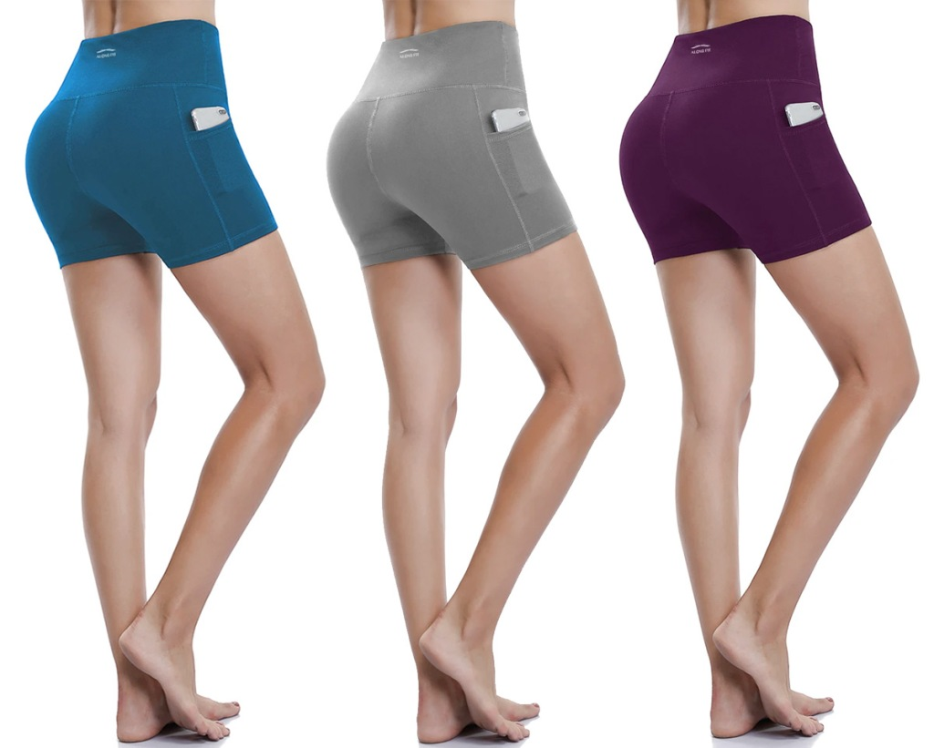 three women modeling workout shorts with pockets in blue, grey, and dark purple colors