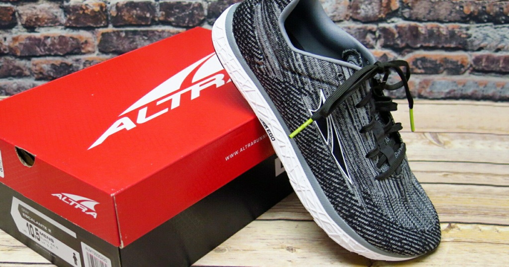 pair of black and white knit running shoes leaning up against a red shoe box in front of a brick wall