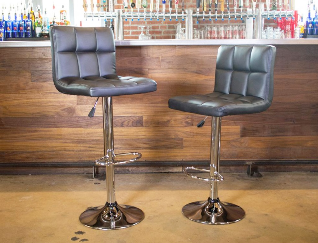 two faux leather cushioned bar stools with low backs at wooden bar