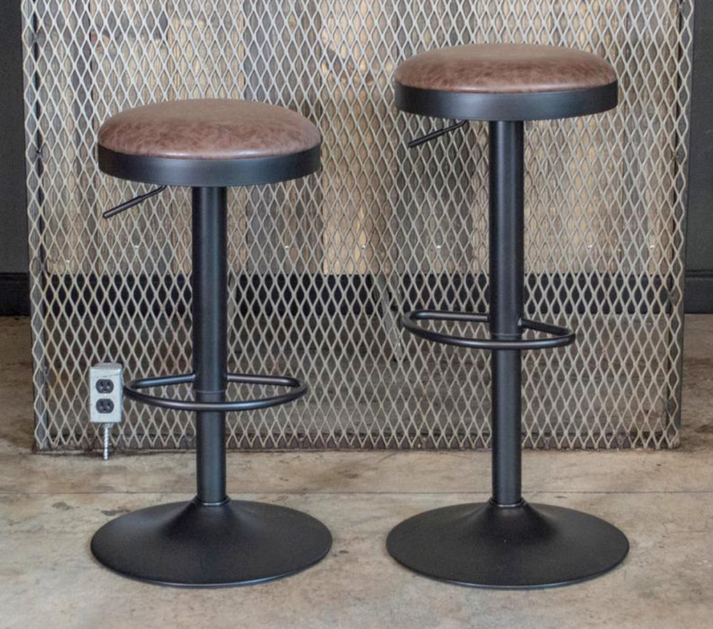 two backless round barstools with brown leather tops and black metal base
