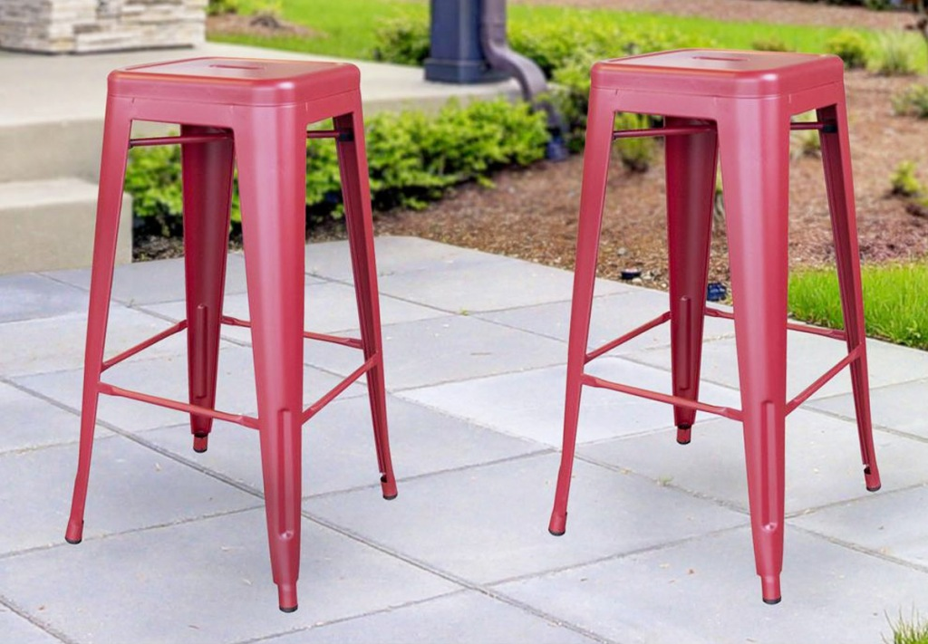 two red industrial style backless metal barstools on outside patio
