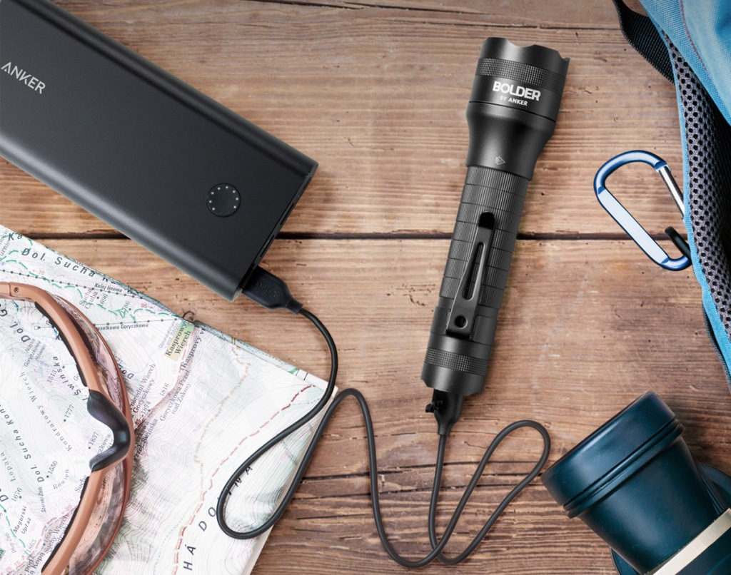 black flashlight connected to charging cord laying on wood table near other travel supplies