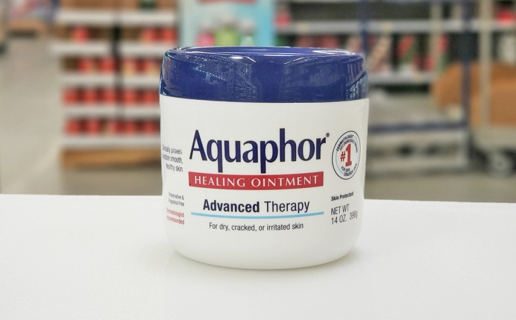 white and blue container of Aquaphor Healing Ointment on white table