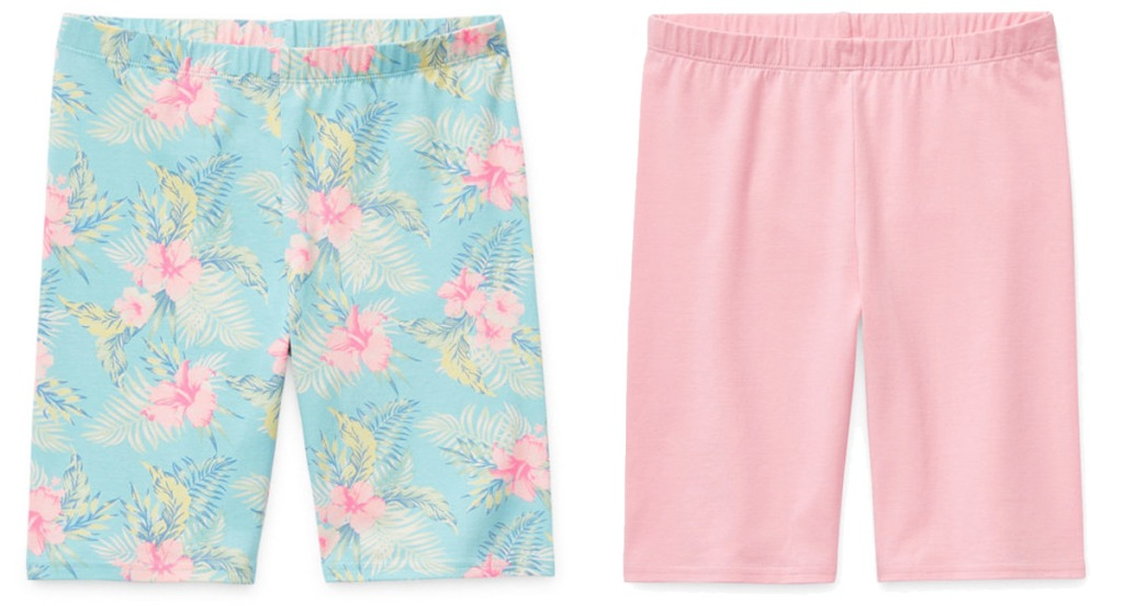 two pairs of girls bike shorts in solid pink and blue with pink tropical flowers