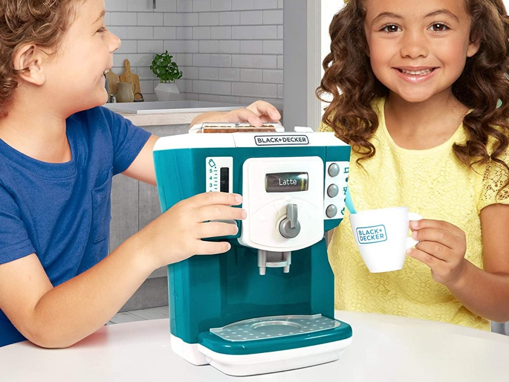boy and girl playing with toy coffee maker