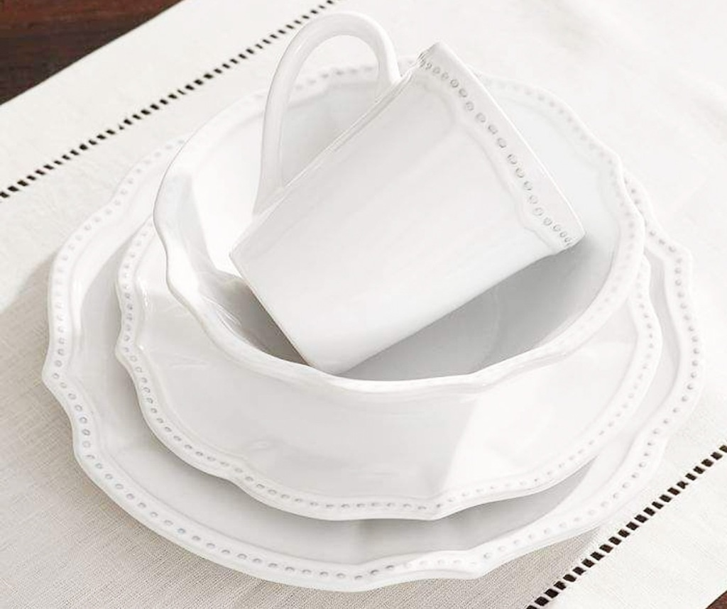 white scalloped edge dinnerware set with dotted print along the edges