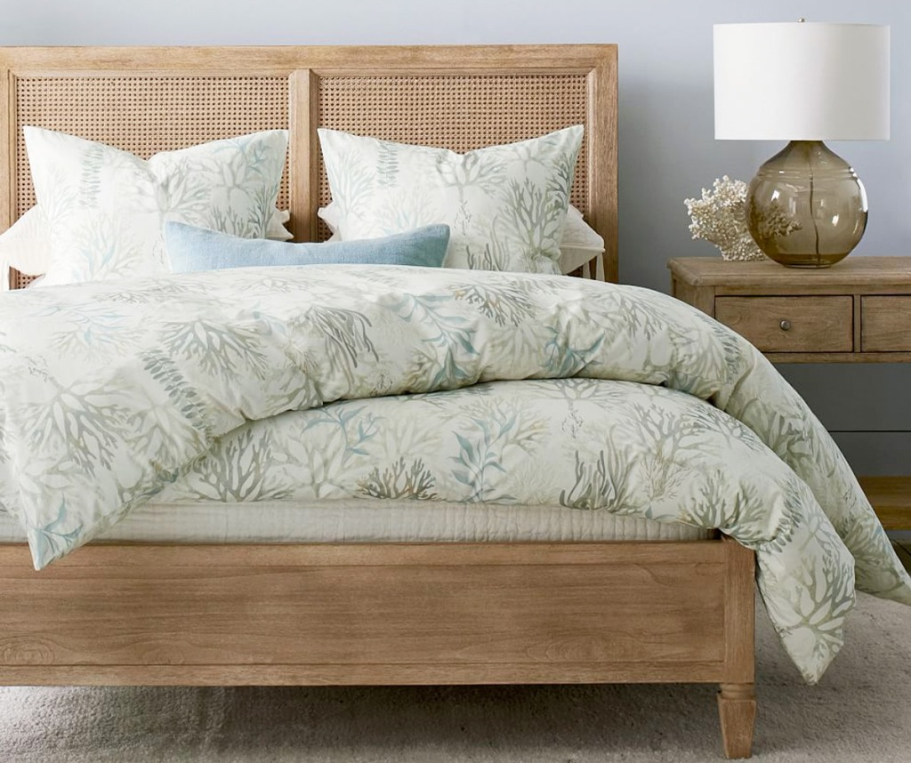 grey and light green coral print duvet cover and pillow shams on bed with wooden frame and matching headboard