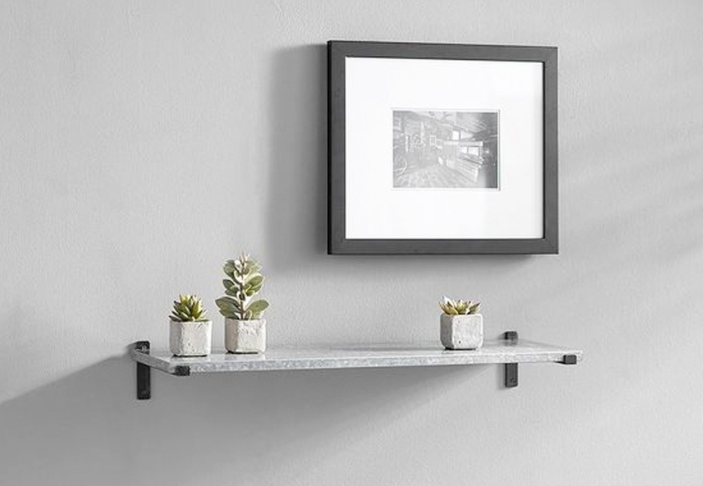 grey floating shelf on wall with succulents on it under a picture frame
