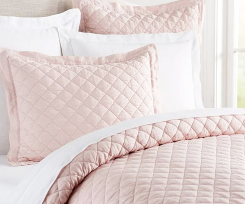 blush pink quilt set on bed with matching pillow shams