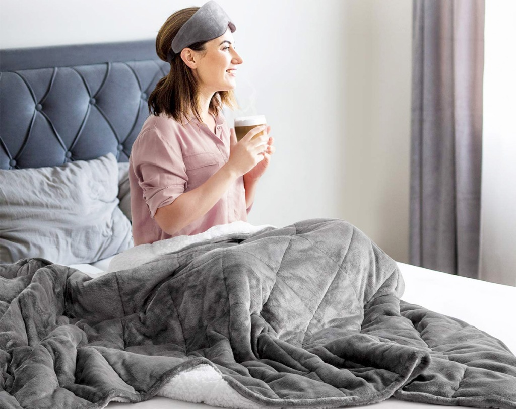 woman sitting in bed drinking coffee under a grey sherpa weighted blanket