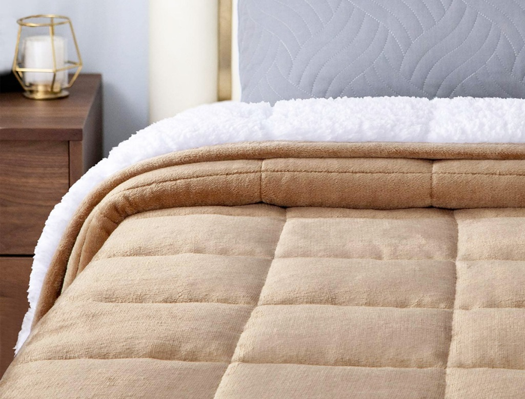 tan colored sherpa fleece blanket on a bed
