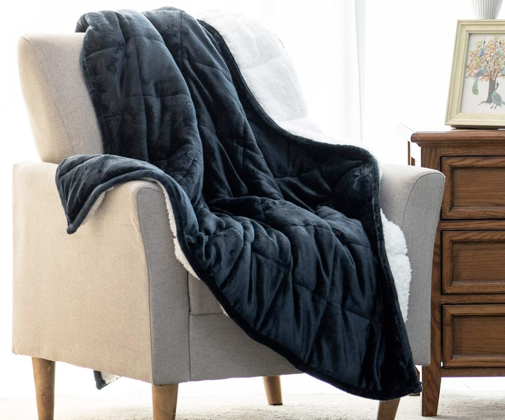 blue sherpa fleece blanket on a cream colored accent chair
