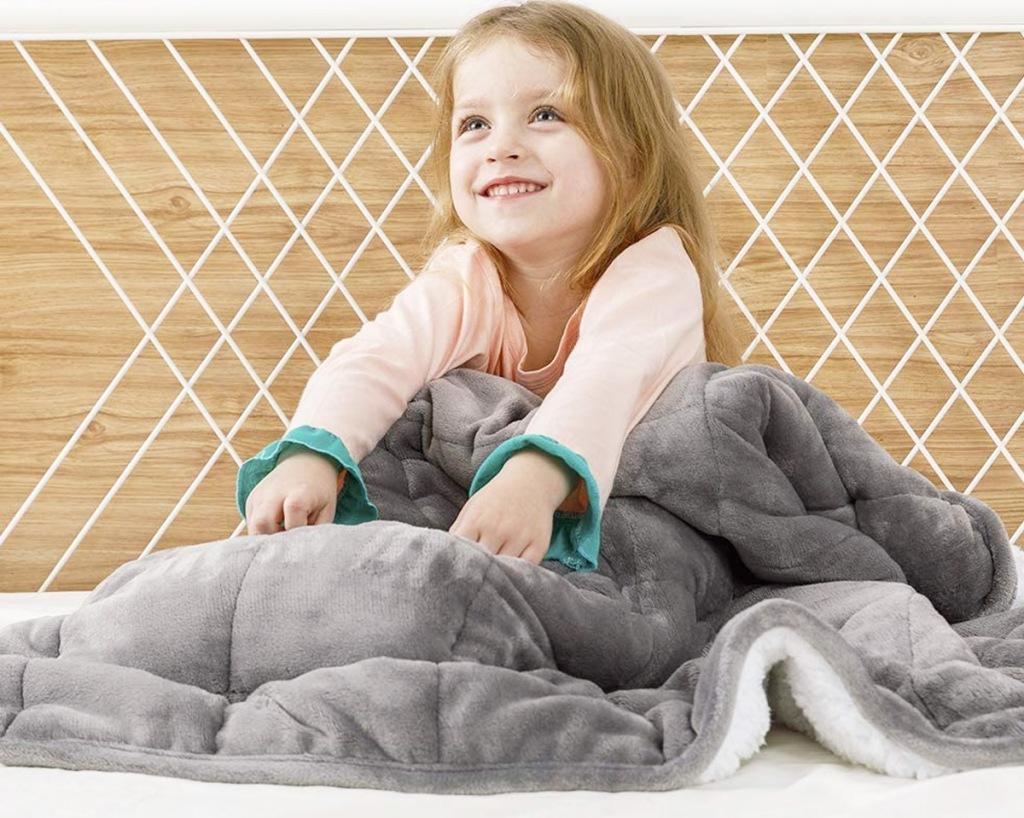 girl in pink pajamas under a grey sherpa fleece weighted blanket
