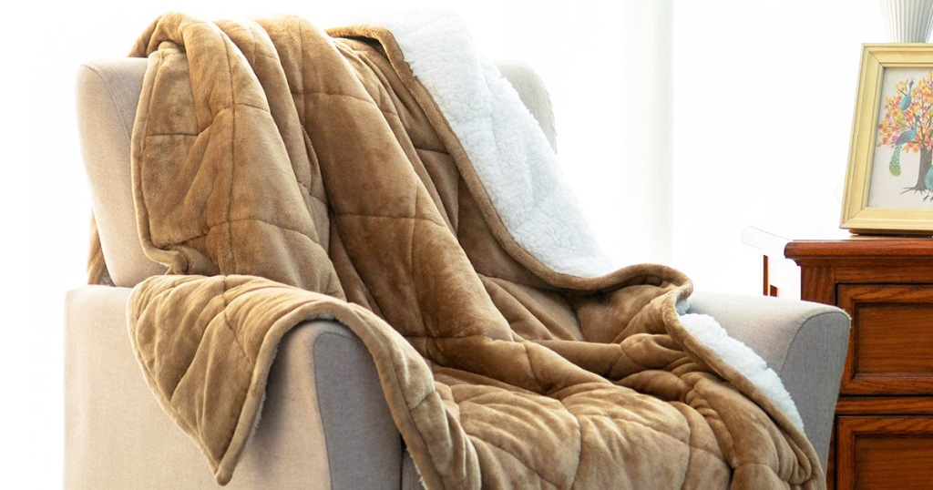 tan sherpa fleece weight blanket on a cream colored accent chair