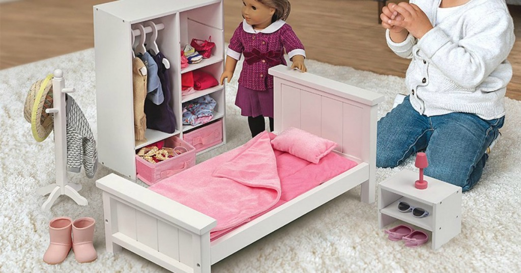 girl playing with doll and doll bedroom furniture