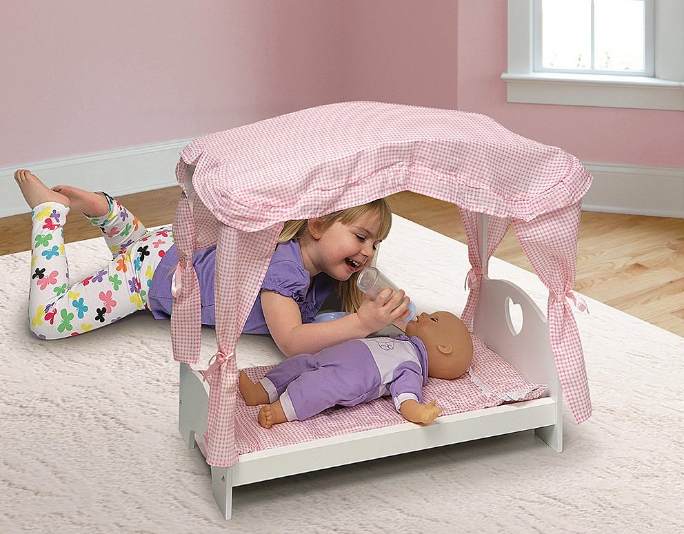 girl playing with doll laying in Badger Basket Canopy Bed