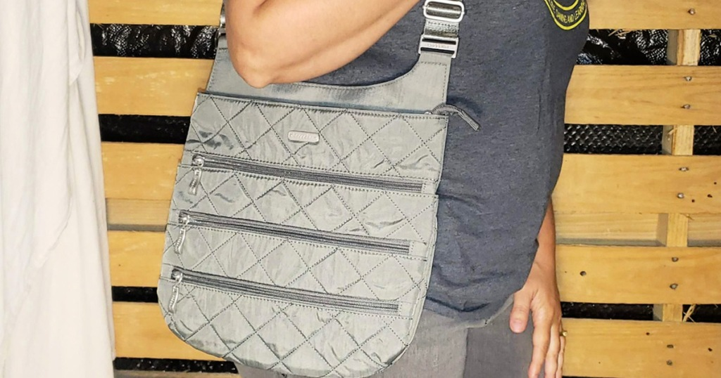 woman wearing a grey quilted crossbody bag with three exterior zippered pockets