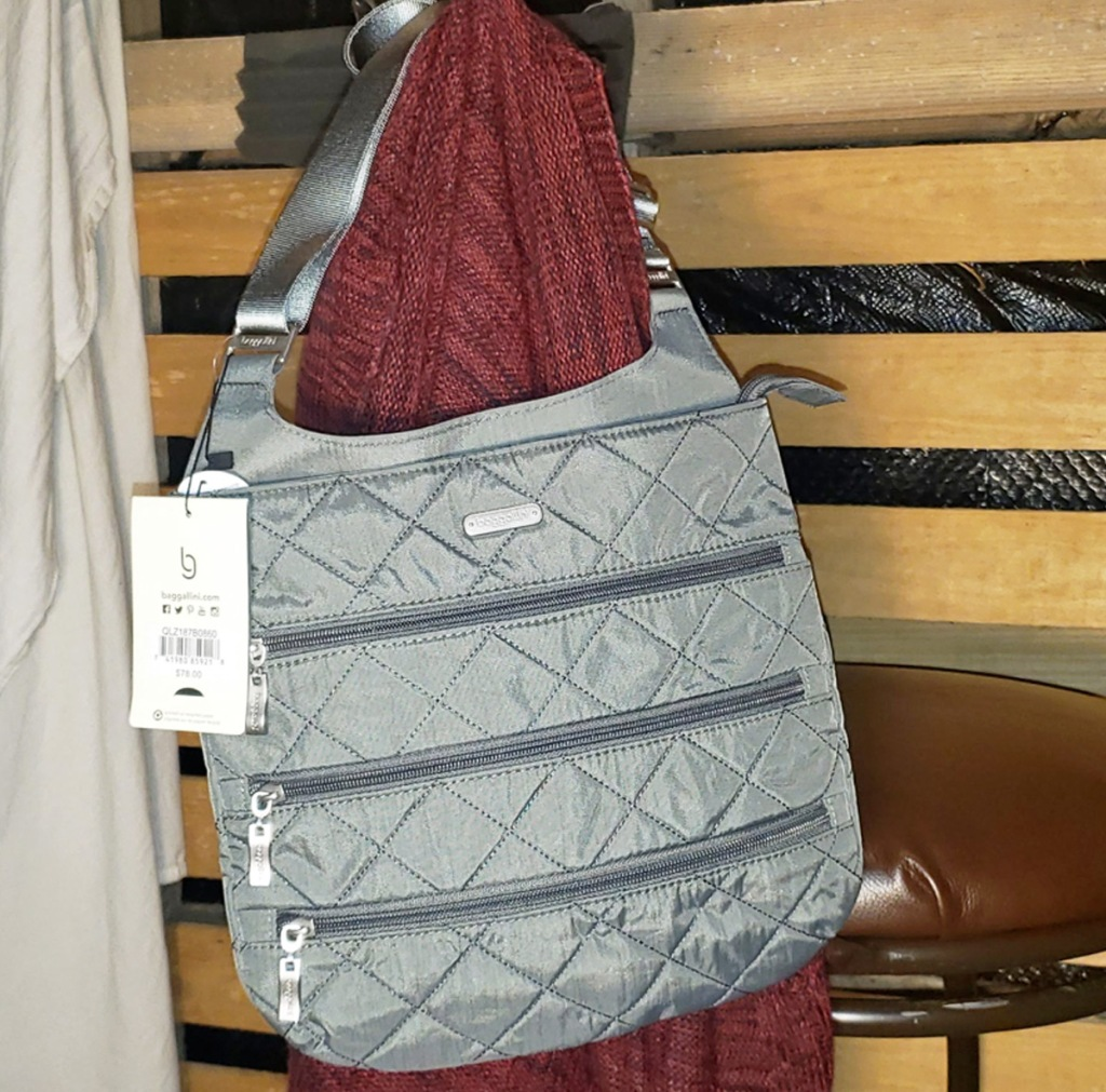 grey quilted crossbody bag with three exterior zippered pockets hanging on a mannequin