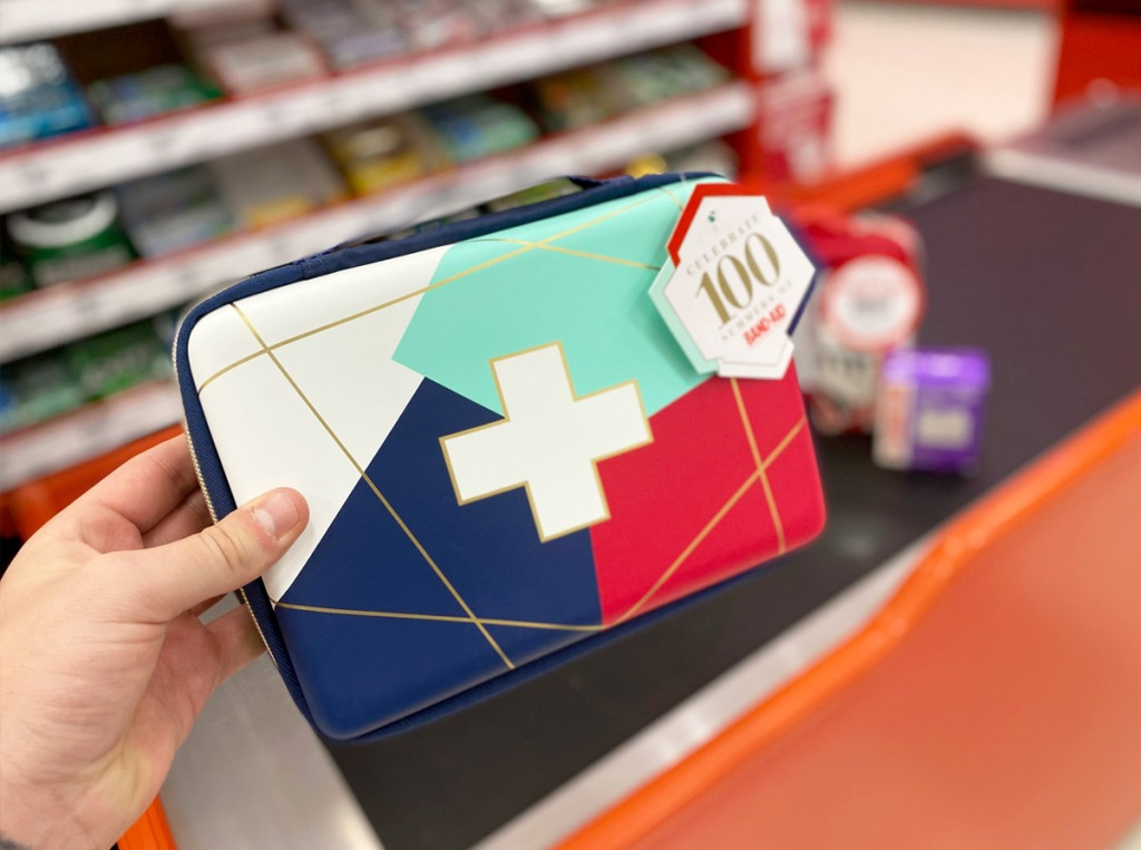 person holding up a geometric print first aid bag in white, green, blue, and red colors with gold lines