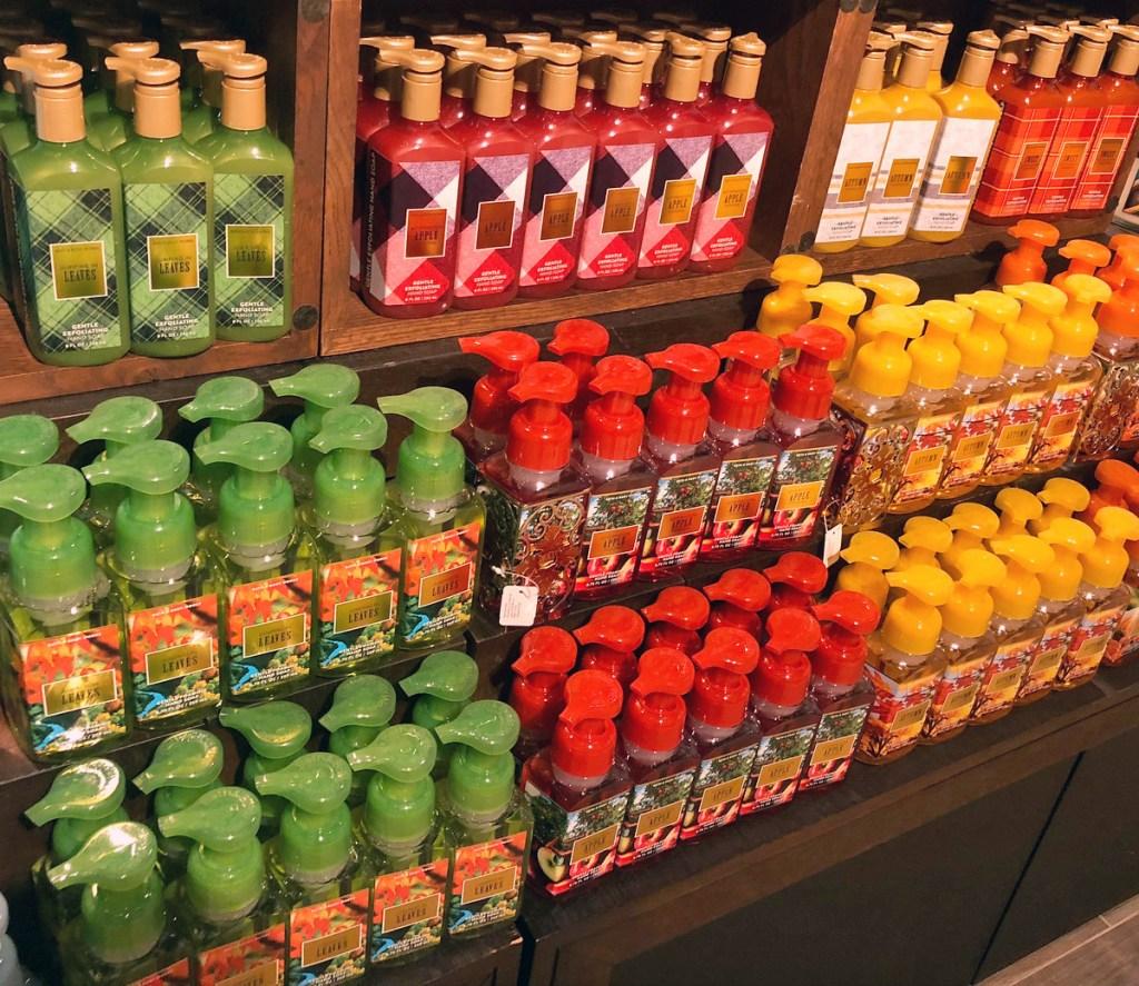 wooden shelves full of fall themed Bath & Body Works hand soaps