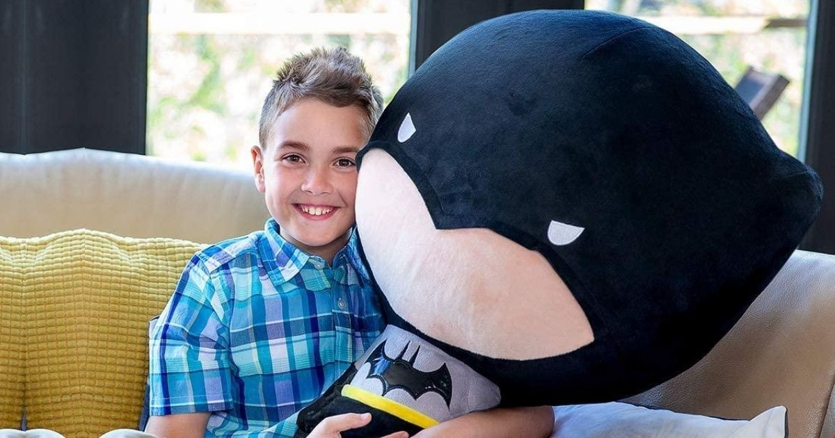 giant head batman toy with little boy on couch