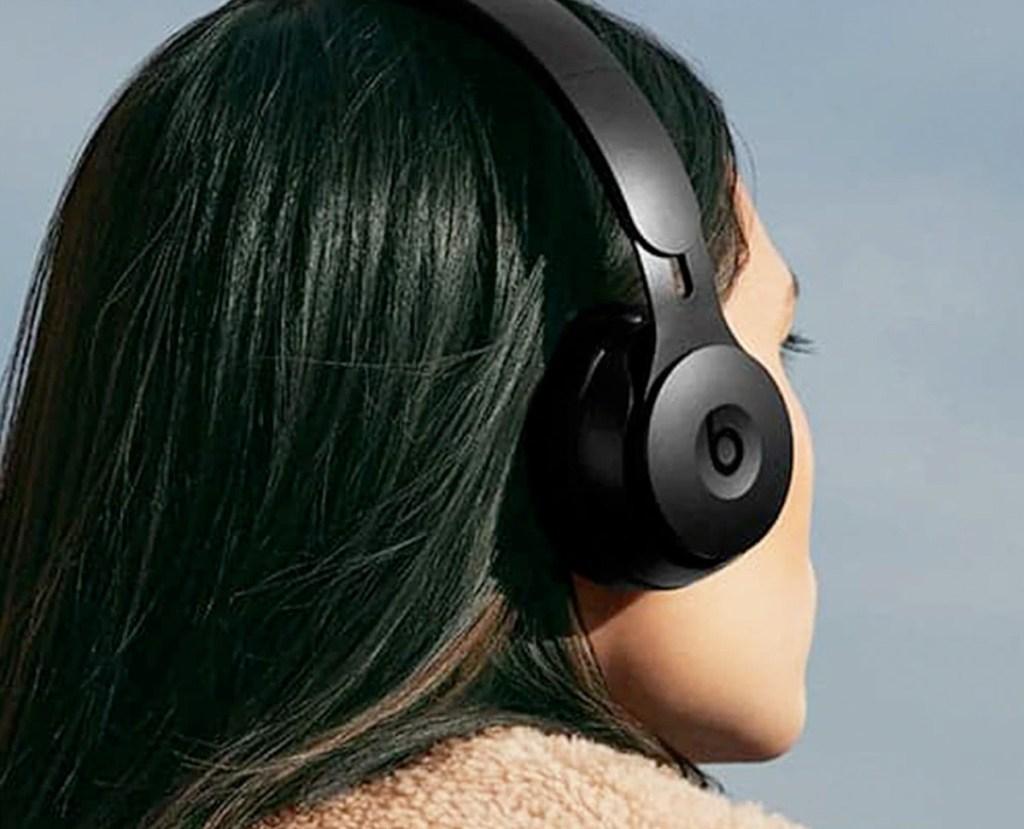 woman with black hair wearing a pair of black beats on-ear headphones