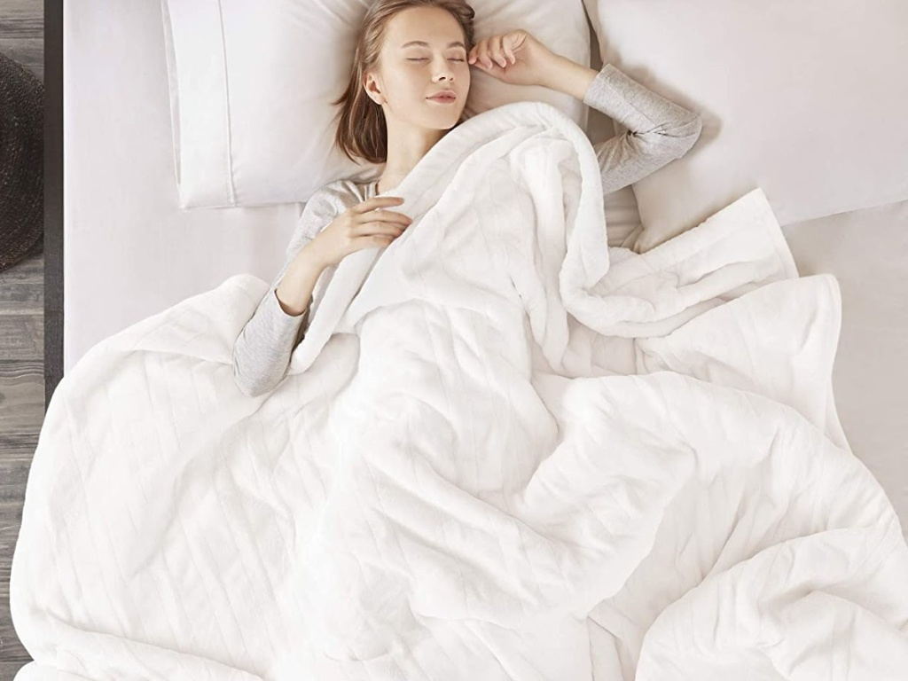 woman laying in bed with white electric blanket