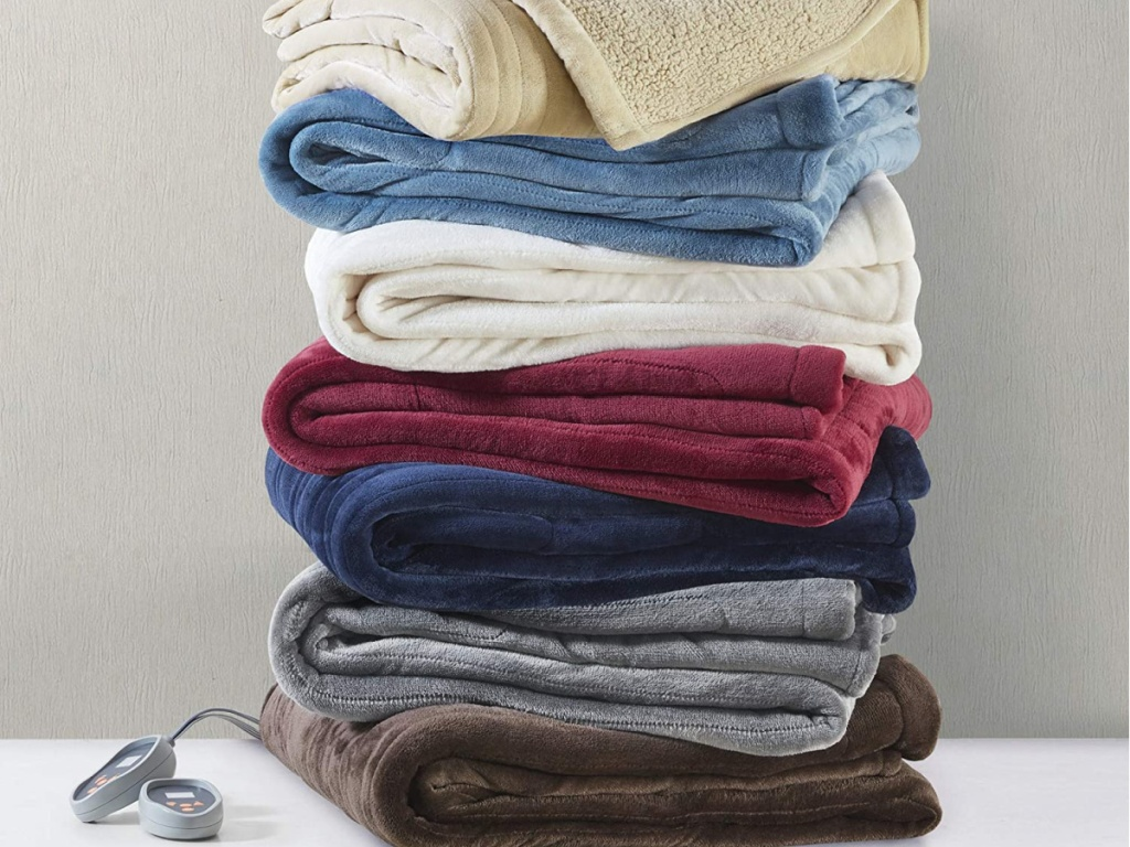 various colored electric blankets folded and stacked in a pile