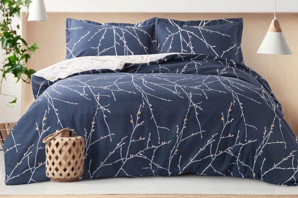 bed with tree branch duvet cover on it