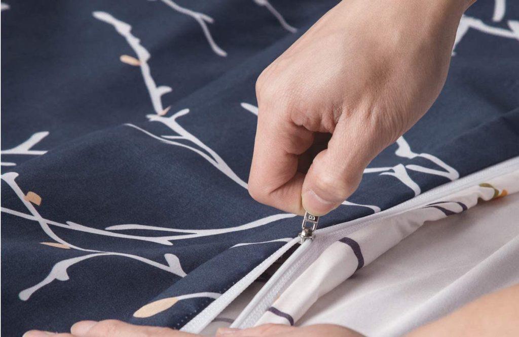 hands zipping up a duvet cover
