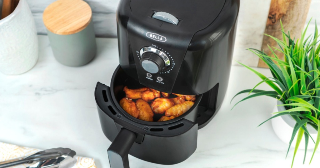 black air fryer sitting open with chicken wings on a kitchen counter