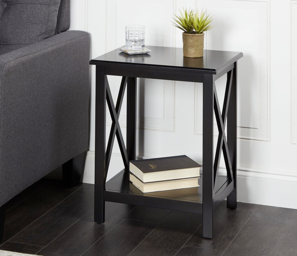 wood side table in black finish with wooden x's on each side and books on the lower shelf